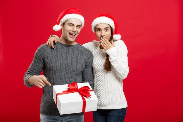 Retrato de joven pareja en navidad suéter apuntando gesto de dedo a los regalos.