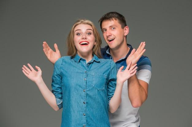 Retrato de una joven pareja de pie contra el fondo gris