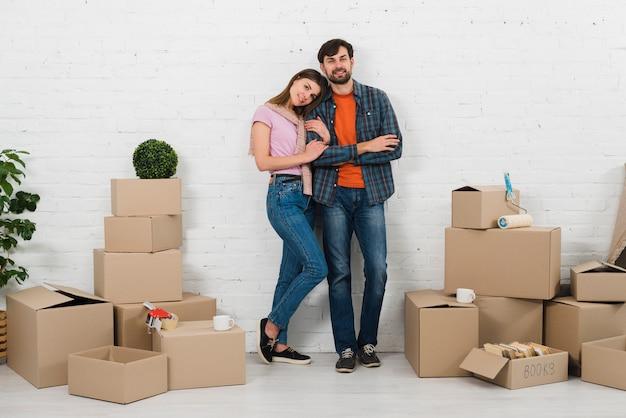 Retrato de joven pareja de pie contra la pared blanca con nuevas cajas de cartón en casa nueva
