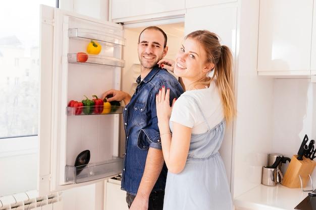 Retrato de joven pareja de pie delante de un refrigerador abierto con verduras