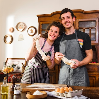 Retrato de joven pareja de pie detrás de la mesa con ingredientes para hornear en la mesa