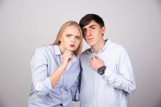 Retrato de una joven pareja posando en la pared gris.