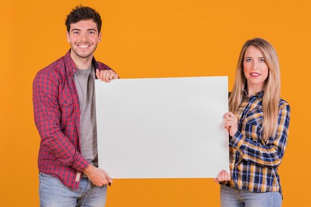 Retrato de una joven pareja que presenta un cartel blanco sobre un fondo naranja