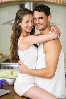Retrato de joven pareja romántica abrazados en encimera de cocina