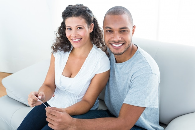 Retrato de la joven pareja sentada en el sofá en casa