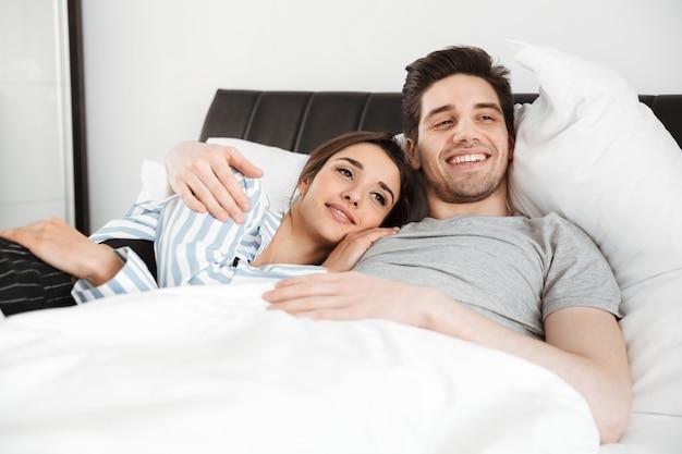Retrato de una joven pareja sonriente acostado