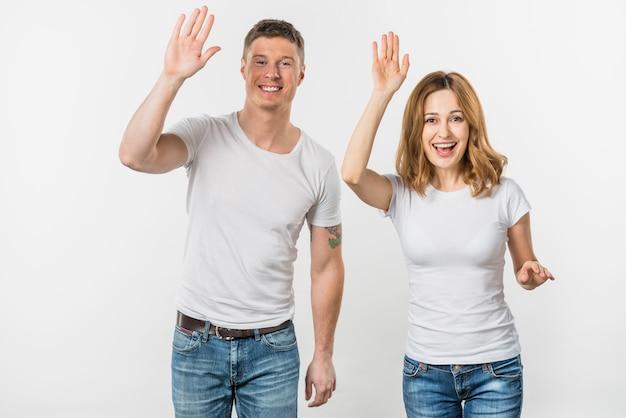 Retrato de una joven pareja sonriente agitando sus manos mirando a la cámara