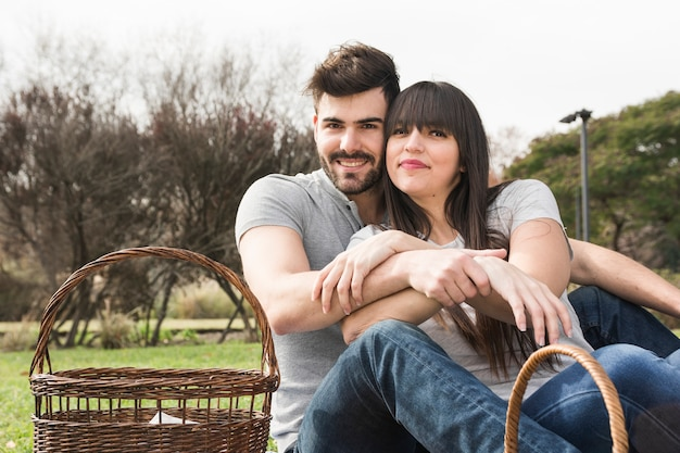 Retrato de la joven pareja sonriente con cesta de picnic en el parque