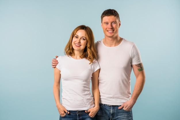 Retrato de una joven pareja sonriente contra el fondo azul