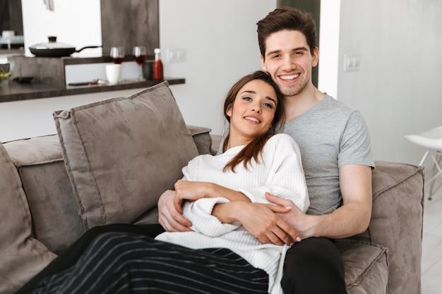 Retrato de una joven pareja sonriente descansando en un sofá