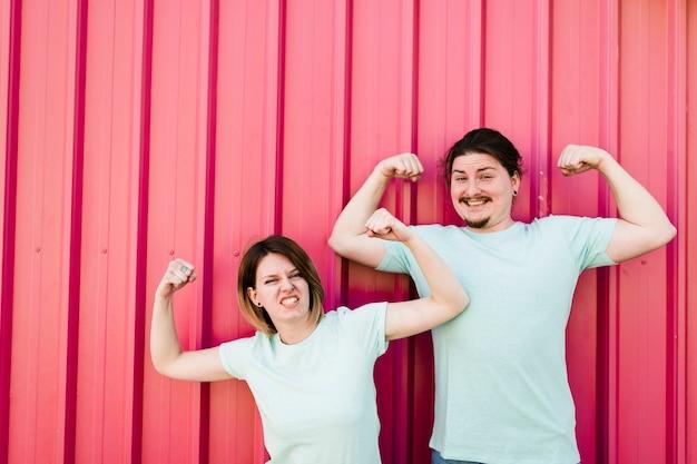 Retrato de una joven pareja sonriente flexionando sus brazos contra la lámina de hierro corrugado