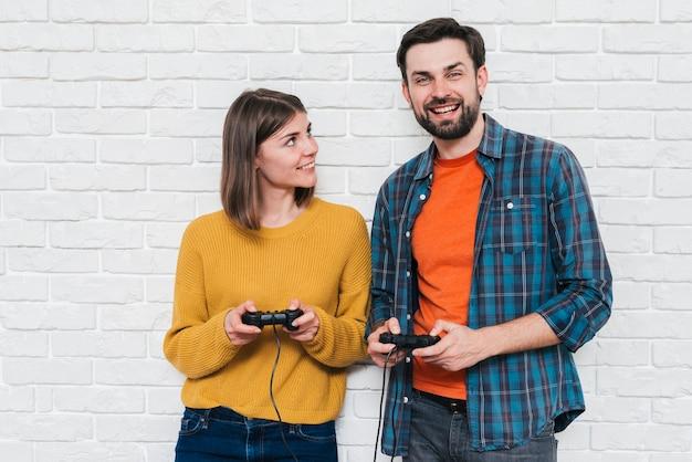 Retrato de una joven pareja sonriente jugando videojuegos con consola