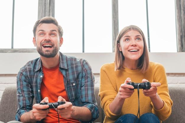 Retrato de una joven pareja sonriente jugando videojuegos con joystick