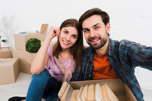 Retrato de una joven pareja sonriente con libros en la caja de cartón tomando sulfuro