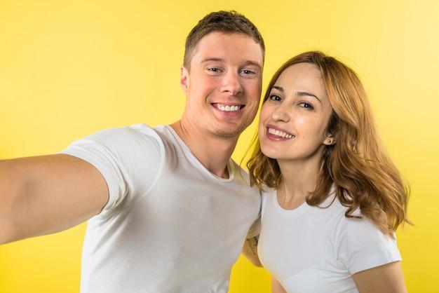 Retrato de una joven pareja sonriente tomando selfie contra el telón de fondo amarillo