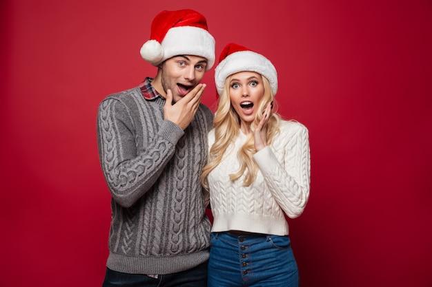 Retrato de una joven pareja sorprendida en sombreros de navidad
