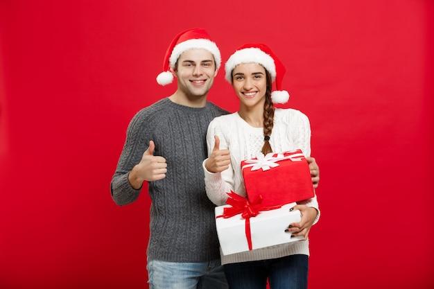 Retrato de joven pareja en suéter de navidad mostrando golpes con regalos.
