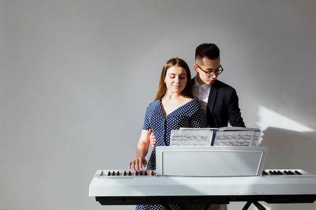 Retrato de joven pareja tocando el piano juntos contra la pared gris
