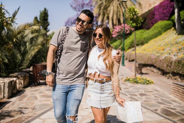 Retrato de joven pareja turista caminando en el parque