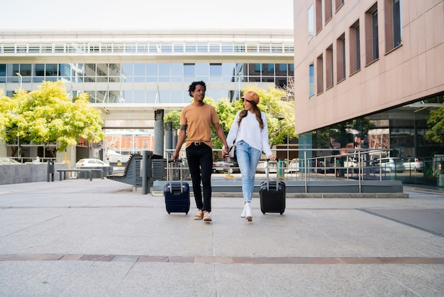 Retrato de joven pareja de turistas llevando maleta mientras camina al aire libre en la calle