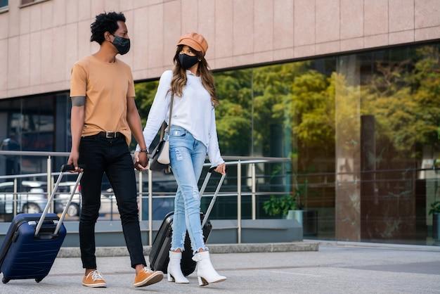 Retrato de joven pareja de turistas con máscara protectora y maleta mientras camina al aire libre en la calle. concepto de turismo. nuevo concepto de estilo de vida normal.