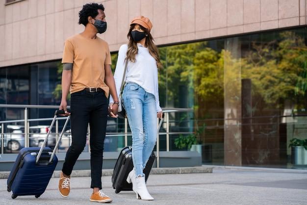 Retrato de joven pareja de turistas con máscara protectora y maleta de transporte mientras camina al aire libre en la calle