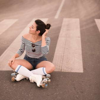 Retrato de una joven patinadora sentada en el camino