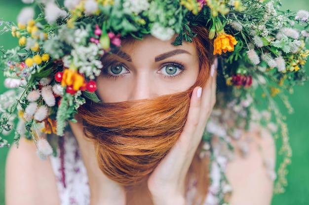 Retrato de una joven pelirroja con una corona de flores en la cabeza, en el contexto de la naturaleza.