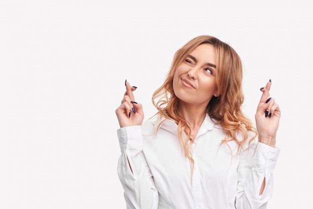 Retrato de una joven pelirroja deseosa con ropa blanca casual, cruzando los dedos, mordiéndose el labio inferior, sintiéndose nerviosa ante un evento importante.
