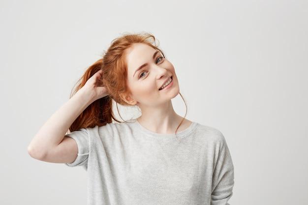 Retrato de joven pelirroja linda chica sonriente tocando el pelo.