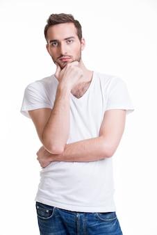 Retrato del joven pensante en casual aislado sobre fondo blanco.