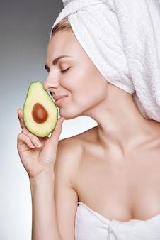 Retrato de una joven con piel sana y sedosa, con una toalla blanca sobre su cabeza sosteniendo una rodaja de aguacate con una piedra