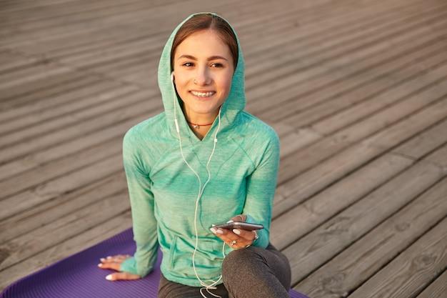 Retrato de joven positiva en ropa deportiva brillante, escuchando su canción favorita en auriculares después de yoga por la mañana y charlando con amigos, sonriendo y mirando a otro lado.