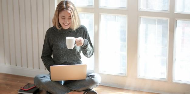Retrato de joven profesional independiente que trabaja en su proyecto y bebe chocolate caliente mientras está sentada cerca de las ventanas