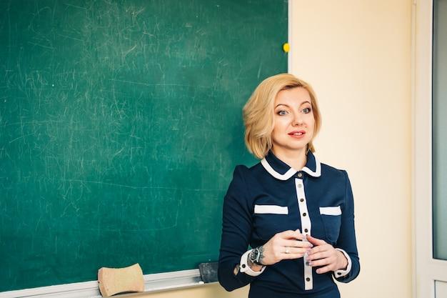 Retrato de joven profesor junto a la pizarra