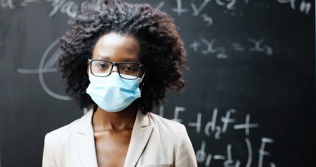 Retrato de joven profesora afroamericana en gafas y máscara médica mirando a cámara en classrom. pizarra con fórmulas sobre fondo. concepto de coronavirus. escolaridad pandémica.