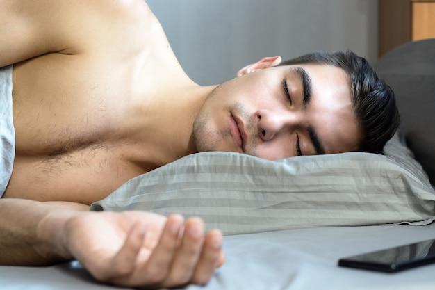El retrato de un joven que duerme en la cama sobre una almohada ortopédica es una forma especial para una columna vertebral saludable.
