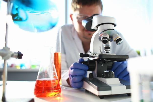 Retrato de un joven químico mirando en binoculares