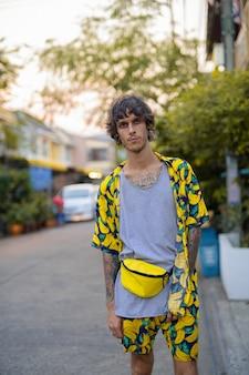 Retrato de joven rebelde de pie en las calles al aire libre