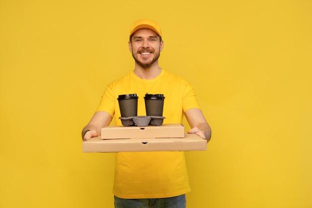 Retrato de joven repartidor en uniforme amarillo con cajas de pizza y café para llevar aislado sobre pared amarilla