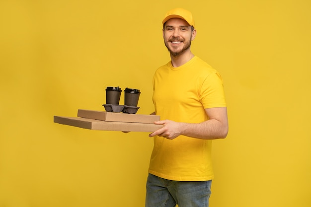 Retrato de joven repartidor en uniforme amarillo con cajas de pizza y cafés para llevar aislado sobre pared amarilla