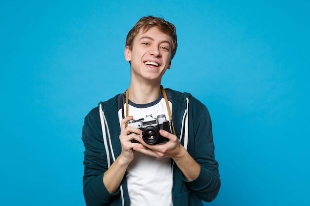Retrato de joven riendo en ropa casual sosteniendo en las manos cámara de fotos vintage retro aislada en la pared azul. personas sinceras emociones, concepto de estilo de vida.