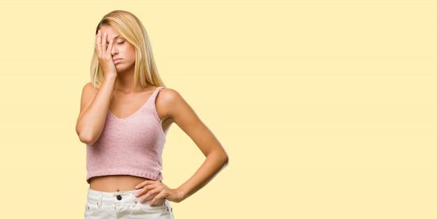 Retrato de una joven rubia bonita preocupada y abrumada, olvidadiza, se da cuenta de algo, expresión de shock por haber cometido un error