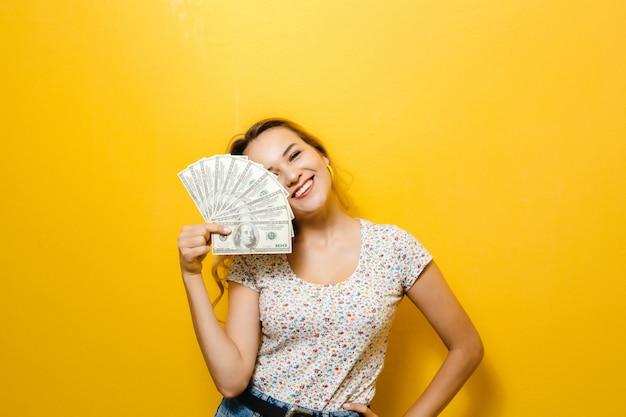 Retrato de una joven rubia feliz celebración de billetes sobre la pared amarilla