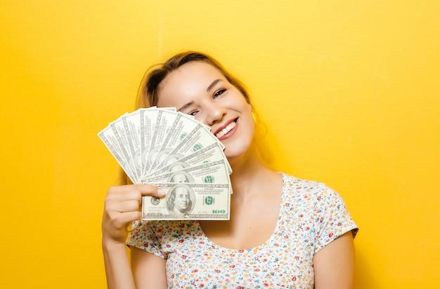 Retrato de una joven rubia feliz celebración de billetes sobre yellowwall