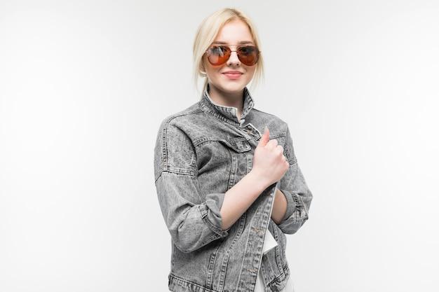 Retrato de joven rubia hermosa con cabello claro parcheado, gafas de sol, camisa blanca, chaqueta gris posa maravillosamente en la cámara