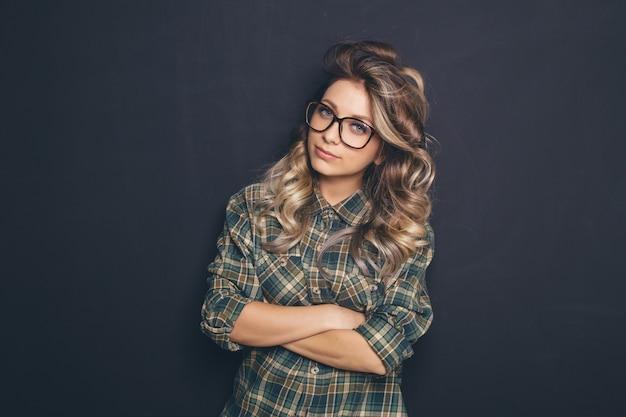 Retrato de una joven rubia hermosa con gafas de moda y ropa casual y posando sobre fondo negro