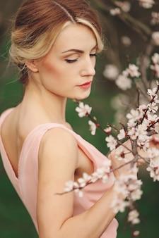Retrato de joven rubia hermosa en vestido rosa cerca de árbol floreciente con flores blancas en un día soleado. primavera, niña cerca de un árbol floreciente
