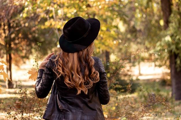 Retrato de una joven rubia con el pelo rizado en una chaqueta de cuero y sombrero negro, camina en el parque en el contexto de un paisaje de otoño. foto de la parte posterior