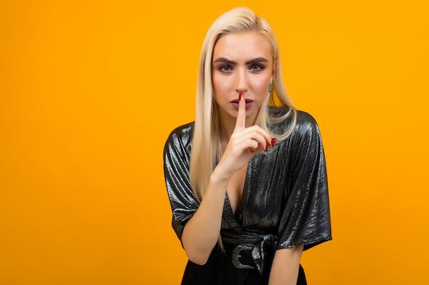 Retrato de una joven rubia pidiendo silencio en un espacio de estudio amarillo